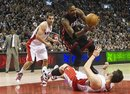 Toronto Raptors forward Andrea Bargnani , right, is knocked down by Miami Heat forward Chris Bosh , center, as Raptors guard Jose Calderon , left, watches on during second-half NBA basketball game action in Toronto, Friday, March 30, 2012.