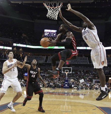 Miami Heat's Dwyane Wade, Center, Sails To The Basket Past Charlotte Bobcats' Bismack Biyombo, Right, As Bobcats' Byron