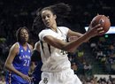 Baylor 's Brittney Griner (42) moves the ball against Kansas' Aishah Sutherland, rear, as Carolyn Davis (21) looks on in the second half of an NCAA women's college basketball game Saturday, Jan. 28, 2012, in Waco, Texas. Griner had seven rebounds, five blocks and 28-points in the 74-46 Baylor win.