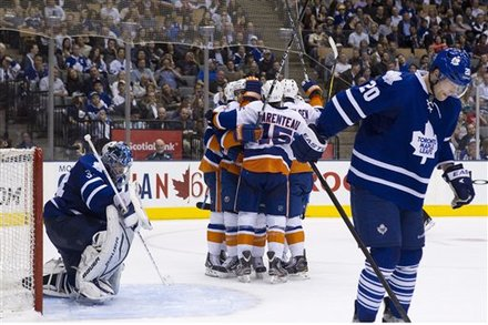 Toronto Maple Leafs Goaltender James Reimer, Left, And David Steckel, Right, React As New York Islanders Celebrate Matt