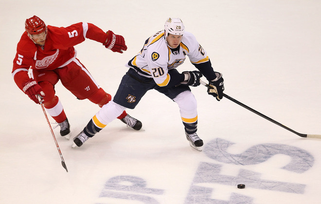 Ryan Suter #20 Of The Nashville Predators Tries To Get Around The Stick Of Nicklas Lidstrom #5 Of The Detroit Red