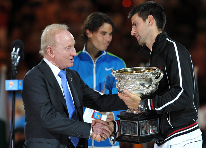 Novak Djokovic Of Serbia (R) Is Presented With The Trophy By Australian Tennis Legend Rod Laver (C) As He Celebrates