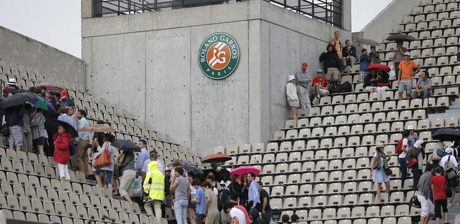 Spectators Hide Under Umbrellas