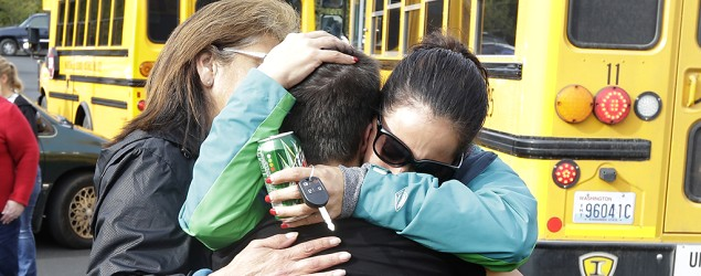 People embrace in front of school busses at a church, Friday, Oct. 24, 2014, where students were taken to be reunited with parents following a shooting at Marysville Pilchuck High School in Marysville, Wash. (AP Photo/Ted S. Warren)