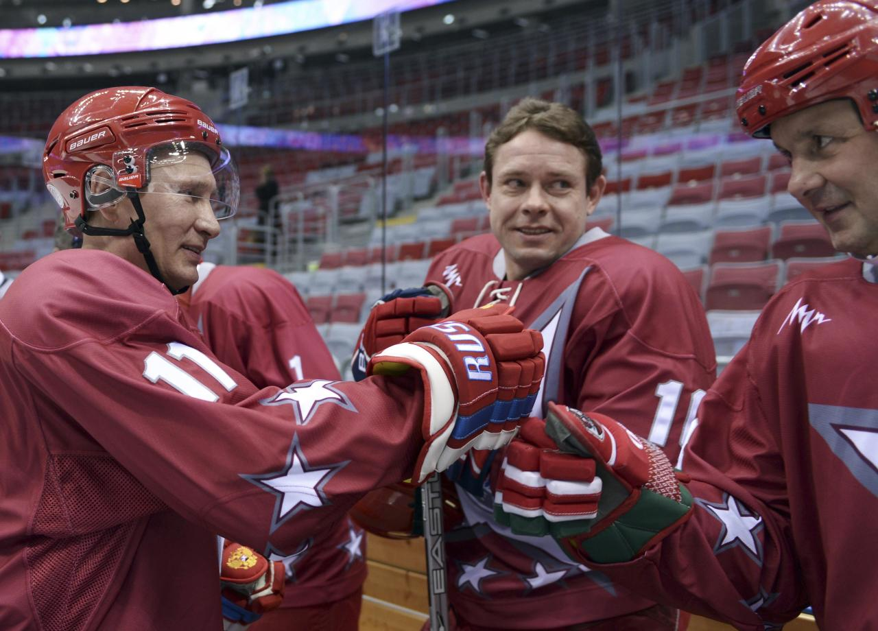 Russian President Vladimir Putin (L) speaks with former ice hockey player Pavel Bure (C) during a friendly ice hockey match in the Bolshoi Ice Palace near Sochi January 4, 2014. REUTERS/Alexei Nikolskiy/RIA Novosti/Kremlin (RUSSIA - Tags: POLITICS SPORT OLYMPICS) ATTENTION EDITORS - THIS IMAGE HAS BEEN SUPPLIED BY A THIRD PARTY. IT IS DISTRIBUTED, EXACTLY AS RECEIVED BY REUTERS, AS A SERVICE TO CLIENTS