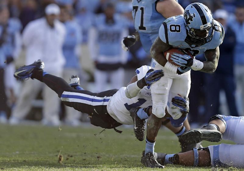 Duke's Jeremy Cash dives to tackle North Carolina's  T.J. Logan (8) during the second half of an NCAA college football game in Chapel Hill, N.C., Saturday, Nov. 30, 2013. Duke won 27-25