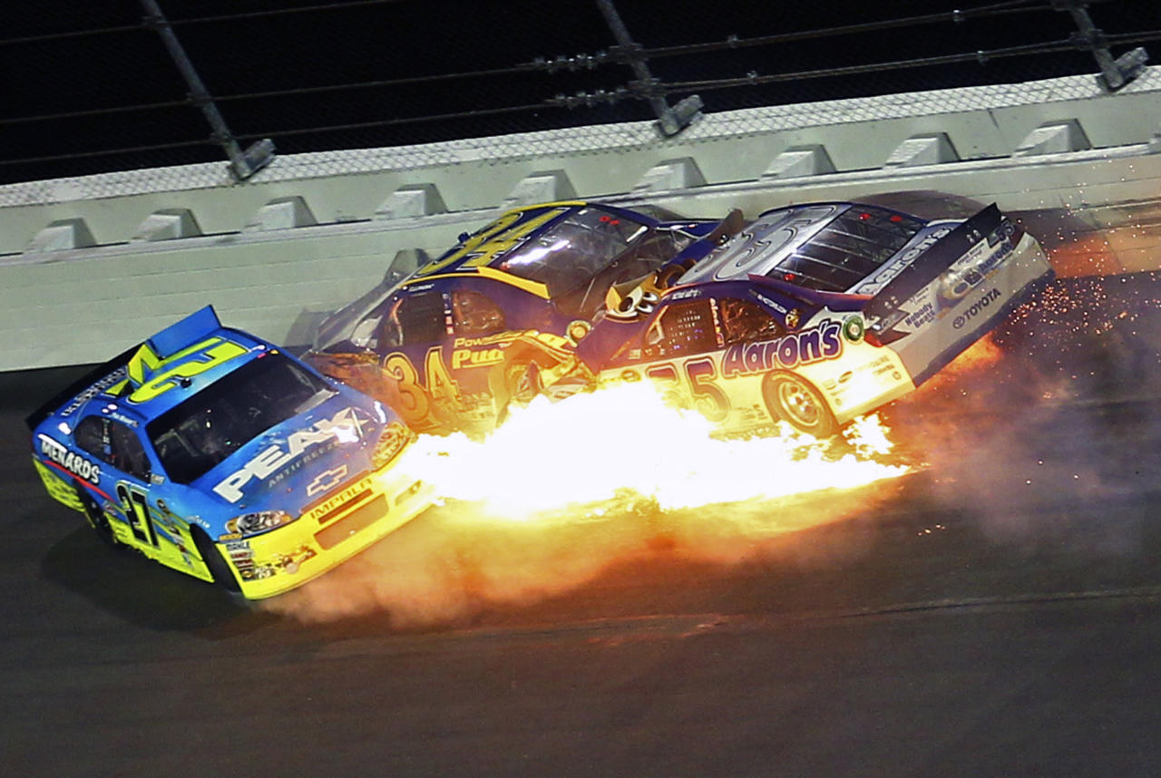 Paul Menard (27), David Ragan (34) and Michael Waltrip (55) wreck coming out of Turn 1 during the NASCAR Budweiser Shootout auto race at Daytona International Speedway, Saturday, Feb. 18, 2012, in Daytona Beach, Fla. (AP Photo/John Moore)