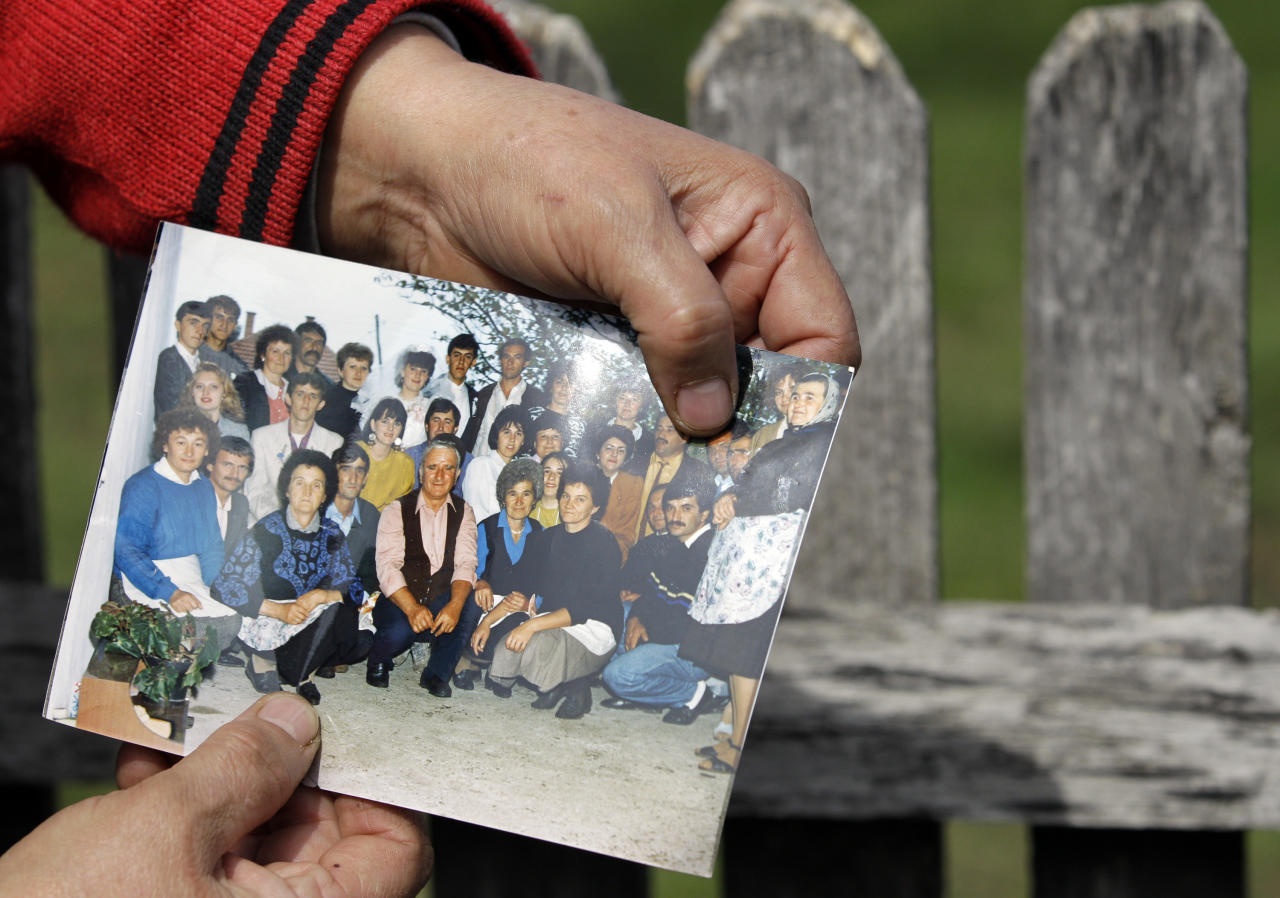 A woman displays Ljubisa Bogdanovic with her left thumb in a group picture in the village of Velika Ivanca, Serbia, Tuesday, April 9, 2013. The 60-year-old man gunned down 13 people, including a baby, in a house-to-house rampage in the quiet village on Tuesday before trying to kill himself and his wife, police and hospital officials said. Belgrade emergency hospital spokeswoman Nada Macura said the man, identified as Ljubisa Bogdanovic, used a handgun in the shooting spree at five houses. The dead included six women. (AP Photo/Darko Vojinovic)