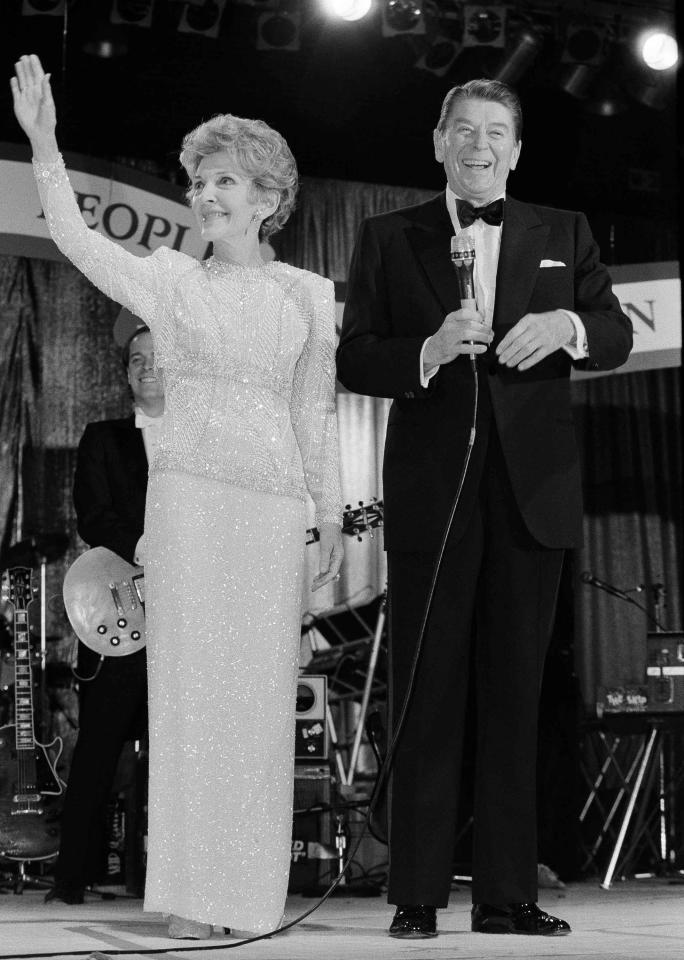 President Ronald Reagan smiles as first lady Nancy Reagan waves to guests at the Ball for Young Americans at the D.C. Armory in Washington, Jan. 21, 1985. President Reagan re-enacted his oath of office earlier in the day in the rotunda of the Capitol. (AP Photo/Ira Schwarz)
