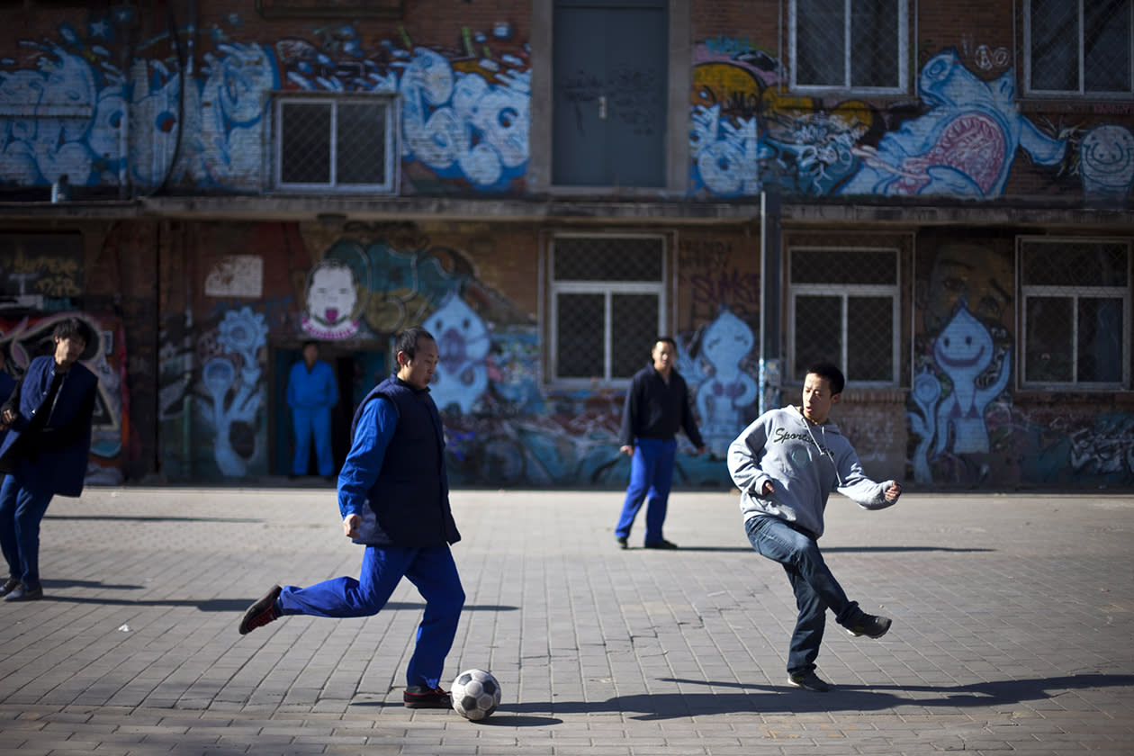 Workers play soccer during their lunch break near a building covered in graffiti.