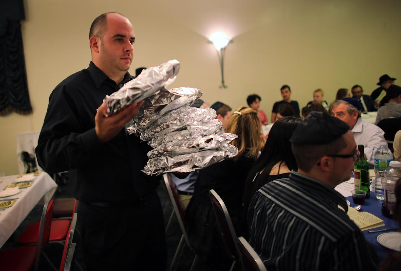 MIAMI BEACH, FL - MARCH 25:  Juan Misas carries matzo wrapped in tin foil to guests during a community Passover Seder at Beth Israel synagogue  on March 25, 2013 in Miami Beach, Florida. The community Passover Seder that served around 150 people has been held for the past 30 years and is welcome to anyone in the community that wants to commemorate the emancipation of the Israelites from slavery in ancient Egypt.  (Photo by Joe Raedle/Getty Images)