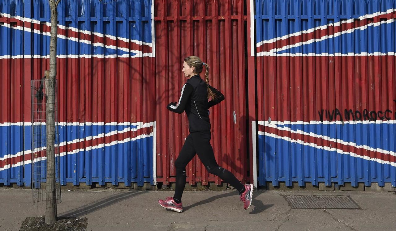 <p>A woman runs past fencing painted in the colors of the British union flag in east London, Britain, Feb. 18, 2017. (Photo: Toby Melville/Reuters) </p>