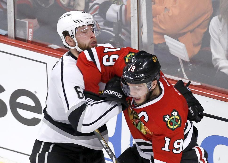 Chicago Blackhawks center Jonathan Toews (19) battles Los Angeles Kings defenseman Jake Muzzin during the second period of Game 1 of the Western Conference finals in the NHL hockey Stanley Cup playoffs in Chicago on Sunday, May 18, 2014. (AP Photo/Charles Rex Arbogast)