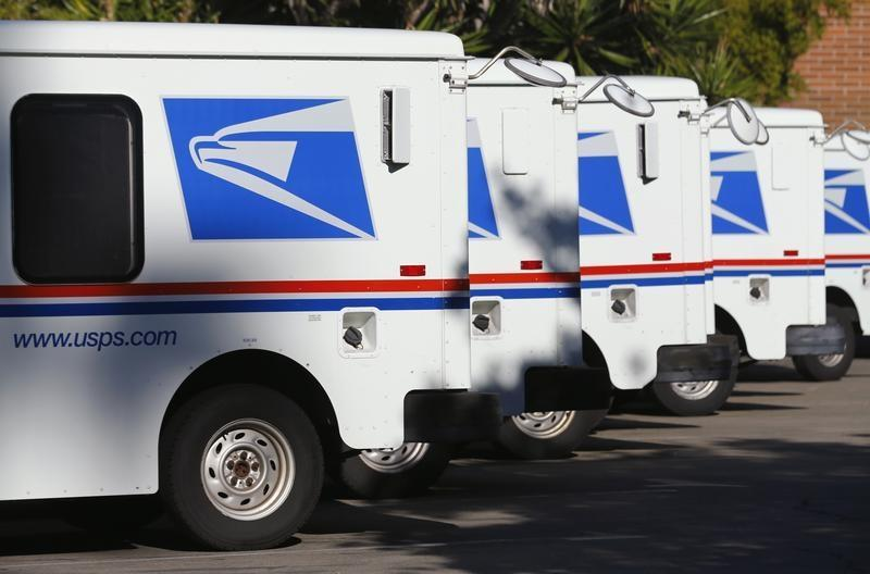 U.S. postal service trucks sit parked at the post office in Del Mar, California