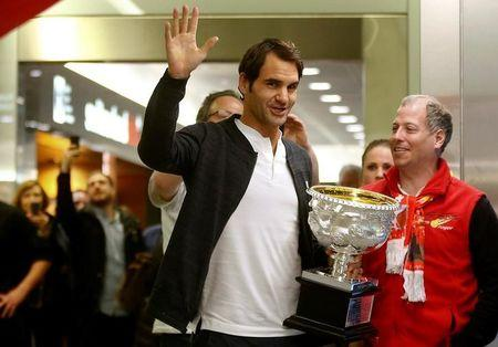 Switzerland's Roger Federer holds his Australian Open trophy as he waves to fans upon his arrival at Zurich airport January 31, 2017.  REUTERS/Arnd Wiegmann
