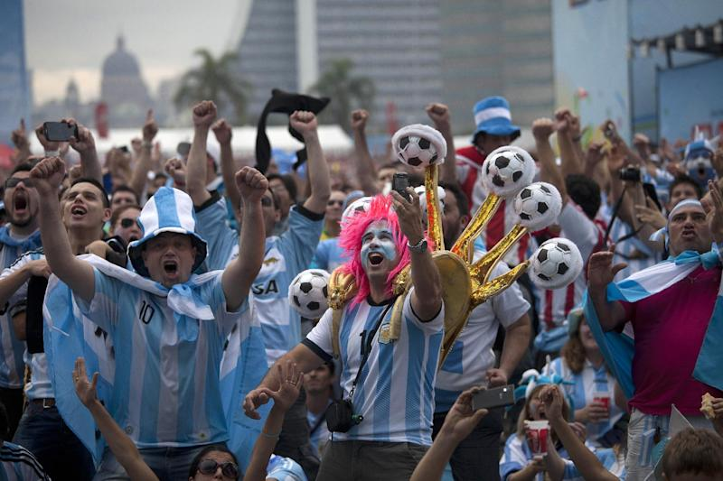 Argentine soccer fans decked out in their national team's colors, celebrate after watching their side score a goal, via a live telecast of the World Cup group F match between Argentina and Nigeria, inside the FIFA Fan Fest area, in Porto Alegre, Brazil, Wednesday, June 25, 2014