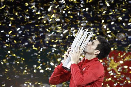 Djokovic of Serbia kisses the trophy after winning the men's singles final match against Del Potro of Argentina at the Shanghai Masters tennis tournament