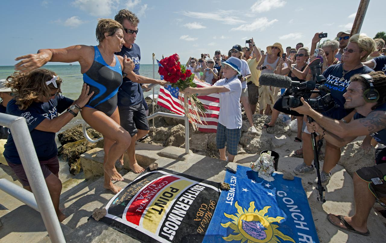 KEY WEST, FL - AUGUST 21: In this photo provided by the Florida Keys News Bureau, endurance swimmer Diana Nyad is helped to shore and welcomed by her team after swimming a short distance from a support boat August 21, 2012 in Key West, Florida. Nyad failed in a fourth attempt to complete a swim across the Florida Straits from Cuba to the Florida Keys.  (Photo by Andy Newman/Florida Keys News Bureau via Getty Images)