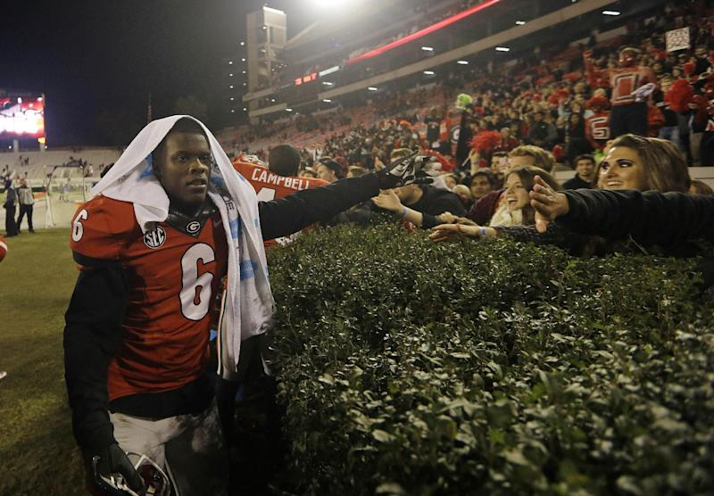 In this Nov. 23, 2013 file photo, Georgia cornerback Shaq Wiggins (6) celebrates with fans after defeating Kentucky 59-17 in an NCAA college football game in Athens, Ga. Wiggins has been released on bail following his arrest for driving with a suspended license. According to Athens-Clarke County police spokeswoman Hilda Sorrow, Wiggins was pulled over Sunday night, Jan. 12, 2014, for speeding after he was clocked driving 52 miles per hour in a 35 mph zone. Sorrow says the arresting officer's routine check on Wiggins' license found Wiggins failed to appear in court on an earlier charge, resulting in the license being suspended