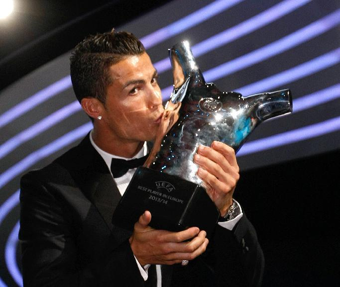 Named the best player of the year, Real Madrid Portuguese forward Cristiano Ronaldo, kisses his trophy during the UEFA Champions League draw, at the Grimaldi Forum, in Monaco, Thursday, Aug. 28, 2014
