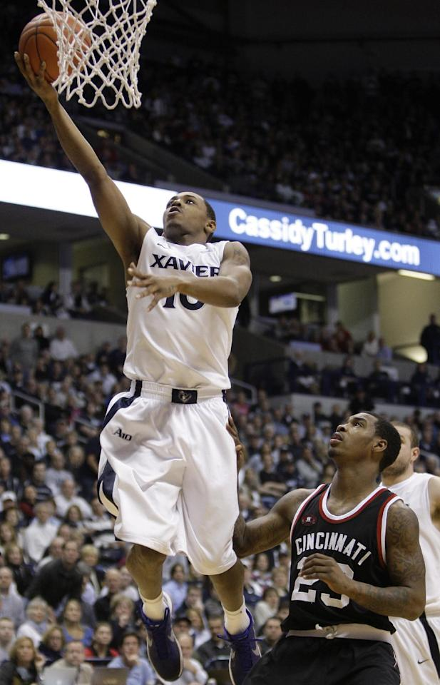 Xavier guard Mark Lyons (10) drives past Cincinnati guard Sean Kilpatrick (23) in the first half of an NCAA college basketball game, Saturday, Dec. 10, 2011, in Cincinnati. (AP Photo/Al Behrman)