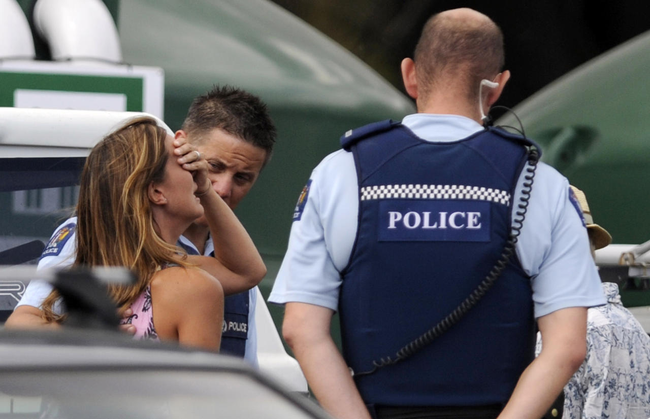 "Police comfort a woman believed to be a family member of a man attacked by a shark at  Muriwai Beach near Auckland, New Zealand, Wednesday, Feb. 27, 2013. Police said a man was found dead in the water after being ""bitten by a large shark."" (AP Photo/Ross Land)"