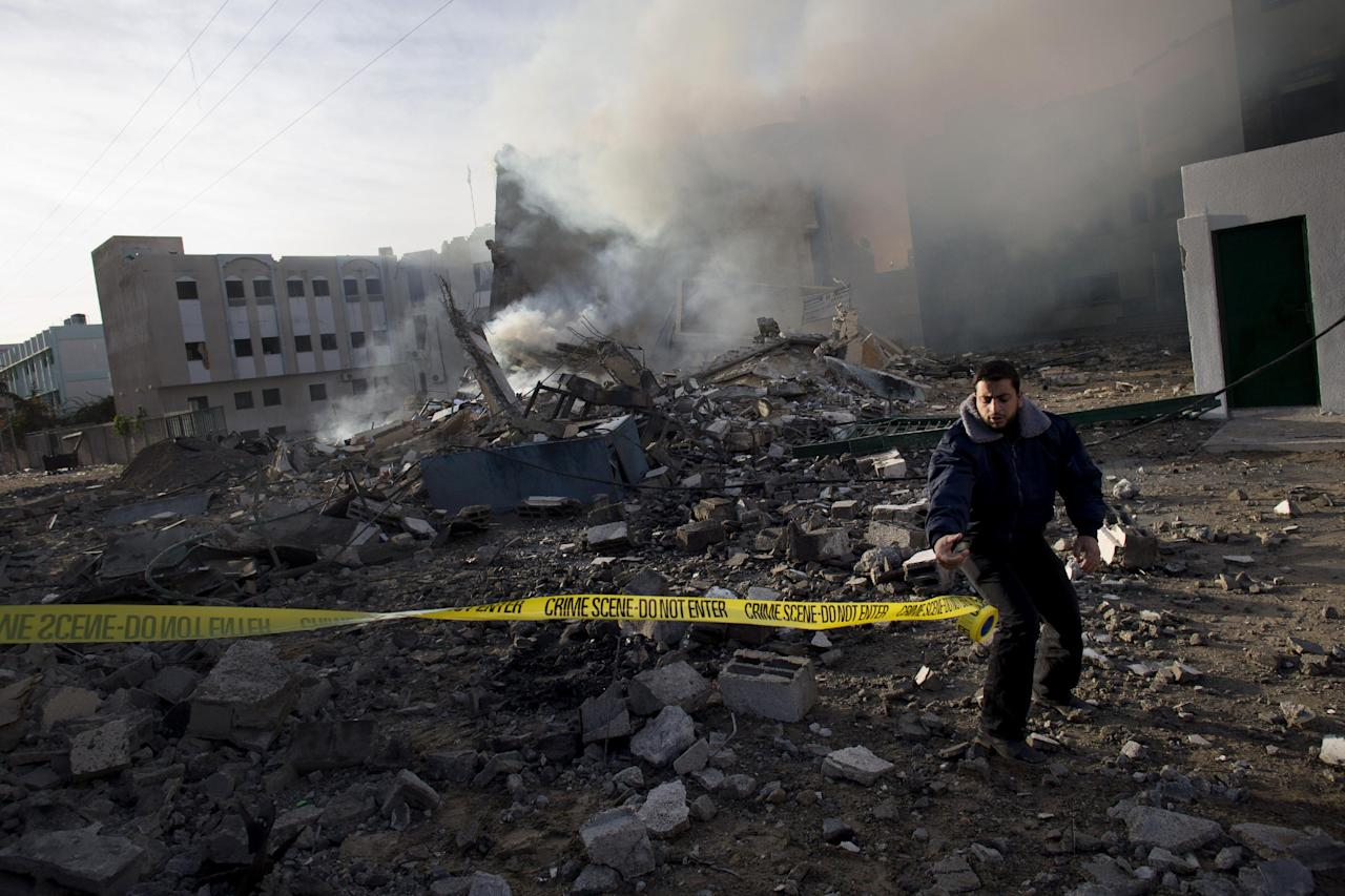 A Palestinian Hamas officer secures the area after an early morning Israeli airstrike on a building that served as a branch of the Interior Ministry in Gaza City, Friday, Nov. 16, 2012. Israel offered to suspend its offensive in the Gaza Strip on Friday during a brief visit by Egypt's premier there if militants refrain from firing rockets at Israel, an official said, but the Palestinians unleashed a fresh salvo. (AP Photo/Bernat Armangue)