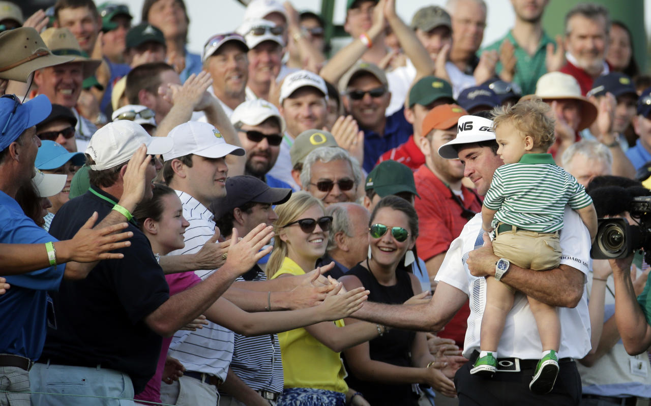 Bubba Watson, carrying his son Caleb, is congratulated by spectators after winning the Masters golf tournament Sunday, April 13, 2014, in Augusta, Ga. (AP Photo/Charlie Riedel)