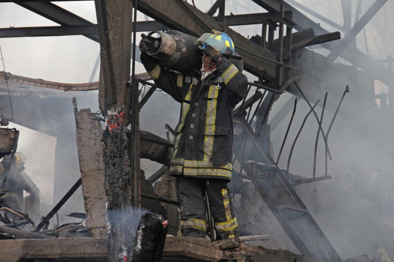 A firefighter carries a gas tank away from a destroyed home after a gas tanker truck exploded on a nearby highway in the Mexico City suburb of Ecatepec early Tuesday, May 7, 2013. The blast killed and injured dozens, according to the Citizen Safety Department of Mexico State. Officials did not rule out the possibility the death toll could rise as emergency workers continued sifting through the charred remains of vehicles and homes built near the highway on the northern edge of the metropolis. (AP Photo/Gabriela Sanchez)