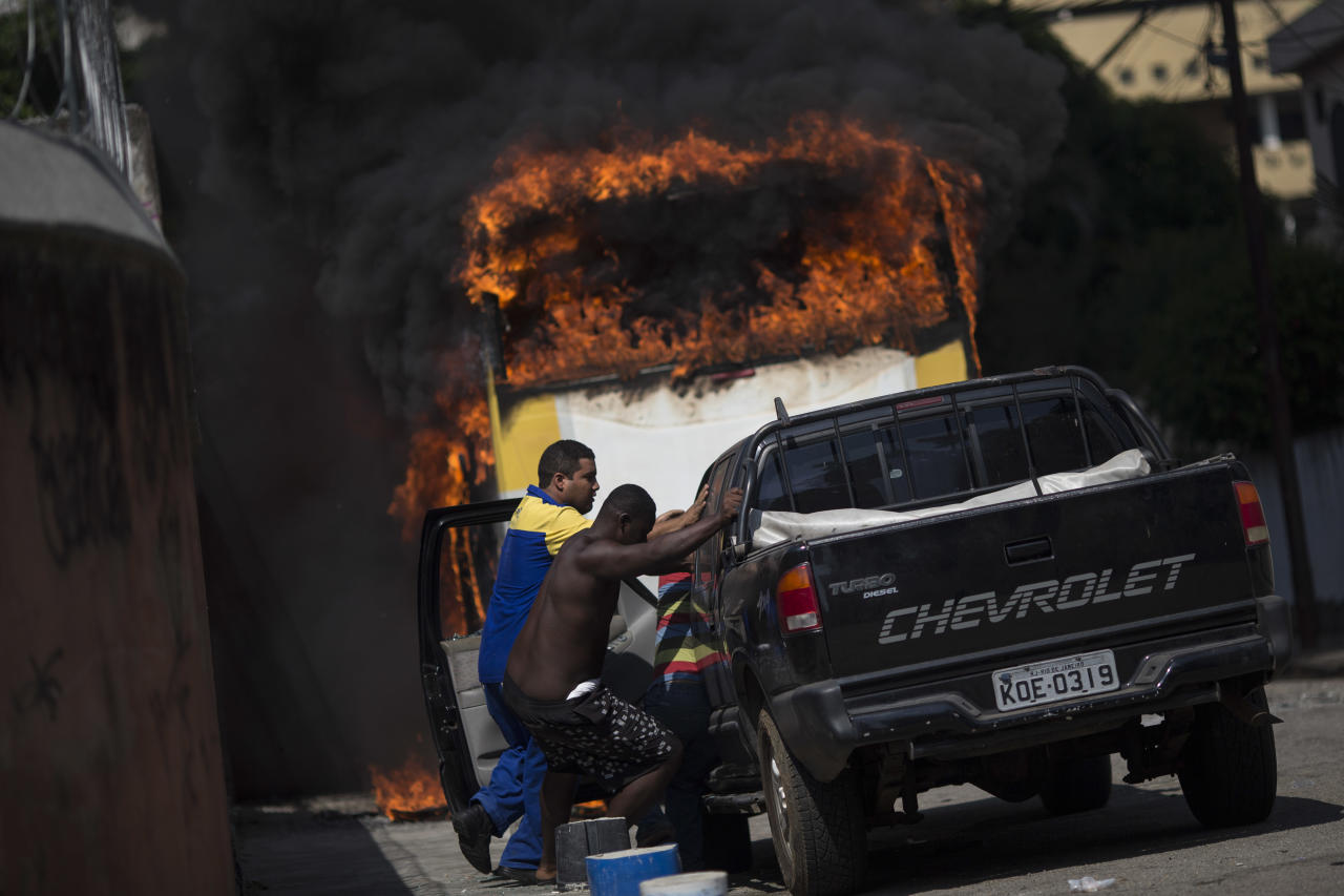 Men move a car away from a burning bus that was set on fire near the area recently occupied by squatters in Rio de Janeiro, Brazil, Friday, April 11, 2014. Squatters in Rio de Janeiro are clashing with police after a Brazilian court ordered that 5,000 people be evicted from abandoned buildings of a telecommunications company. Officers have used tear gas and stun grenades to try to disperse the families. (AP Photo/Felipe Dana)