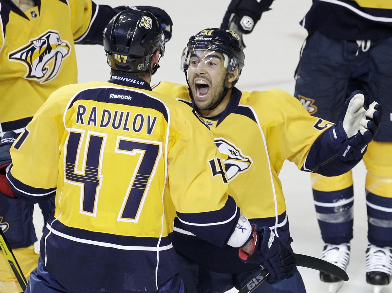 Nashville Predators defenseman Francis Bouillon, right, celebrates with Nashville Predators forward Alexander Radulov (47), of Russia, after Radulov scored against the Detroit Red Wings in the first period of Game 5 of a first-round NHL hockey playoff series on Friday, April 20, 2012, in Nashville, Tenn. (AP Photo/Mark Humphrey)