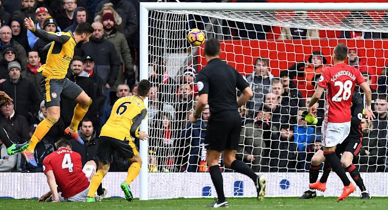 Arsenal's Olivier Giroud (L) scores his team's first goal during the match against Manchester United at Old Trafford on November 19, 2016