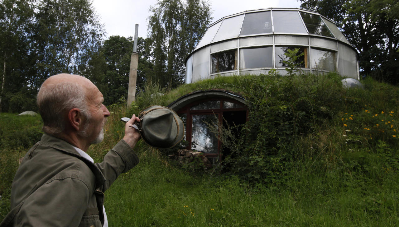 Bohumil Lhota, a 73-year-old builder, stands in front of the house which he built in Velke Hamry, near the town of Jablonec nad Nisou, 100km (62 miles) north-east from Prague, August 7, 2012. Lhota conceptualized the idea to create the unique house and started to build it in 1981, building it close to nature to benefit from the cooler ground temperature. Lhota's house, which is built in 2002, is able to move up and down and rotate on its sides, which allows him to adjust to his preferred window view.  REUTERS/Petr Josek (CZECH REPUBLIC - Tags: BUSINESS CONSTRUCTION SOCIETY SCIENCE TECHNOLOGY) - RTR36EA2