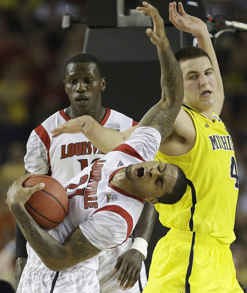 Louisville forward Chane Behanan (21) grabs the ball as Michigan forward Mitch McGary (4) looks on during the first half of the NCAA Final Four tournament college basketball championship game Monday, April 8, 2013, in Atlanta. (AP Photo/Charlie Neibergall)
