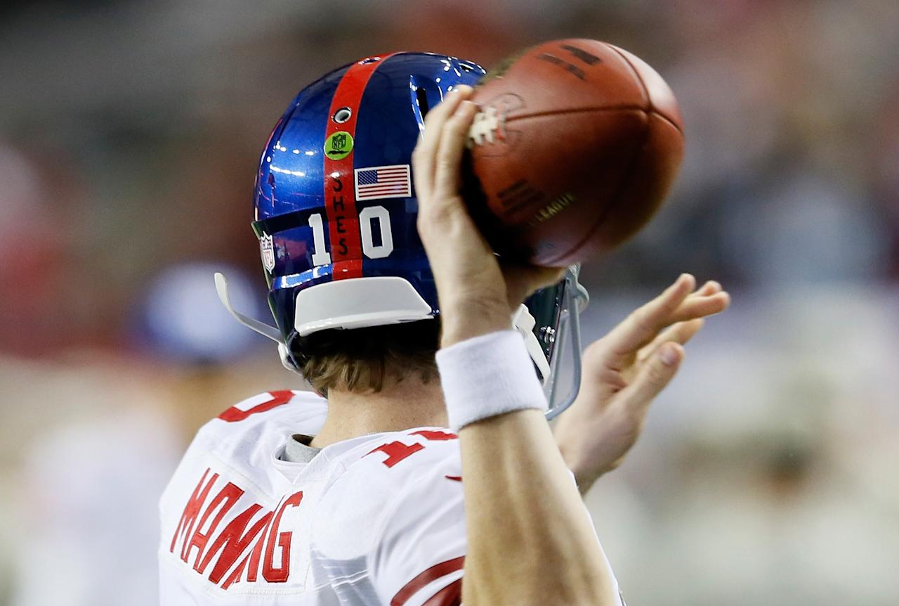 ATLANTA, GA - DECEMBER 16:  Eli Manning #10 of the New York Giants warms up prior to facing the Atlanta Falcons at Georgia Dome on December 16, 2012 in Atlanta, Georgia.  The initials S.H.E.S for Sandy Hook Elementary School in Connecticut are written on his helmet and his teammates' helmets to honor the victims of the school shooting on December 14, 2012.   (Photo by Kevin C. Cox/Getty Images)