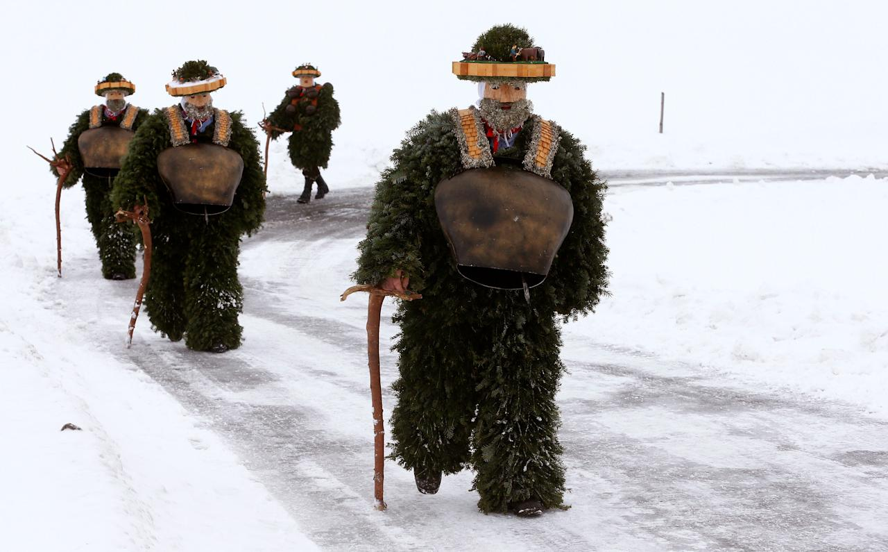 "Men dressed as ""Chlaeuse"", figures that scare away evil spirits, carry round bells and cowbells as they walk on a partially snow-covered road during the traditional ""Sylvesterchlausen"" near the northeastern village of Urnaesch, Switzerland January 13, 2017. REUTERS/Arnd Wiegmann      TPX IMAGES OF THE DAY"