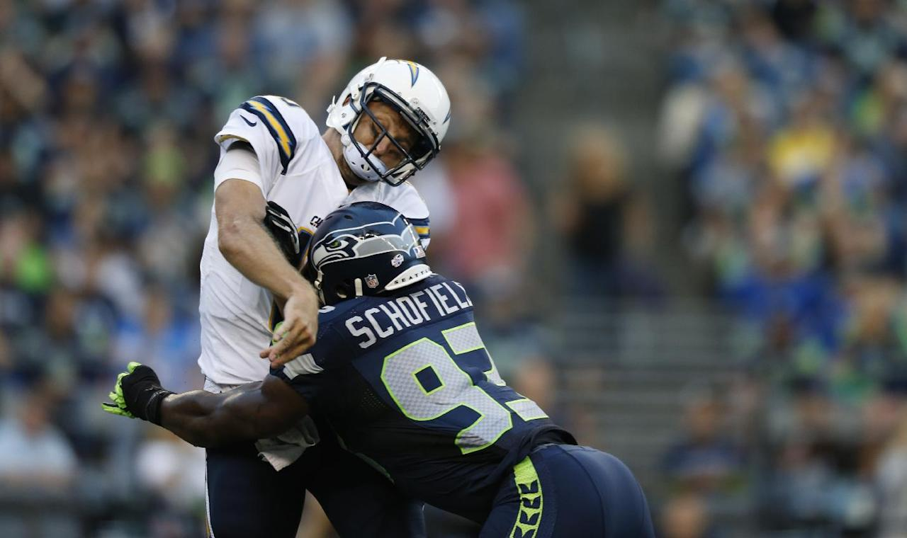 Seattle Seahawks defensive end O'Brien Schofield tackles San Diego Chargers quarterback Kellen Clemens after Clemens released the ball in the first half of a preseason NFL football game, Friday, Aug. 15, 2014, in Seattle. (AP Photo/John Froschauer)