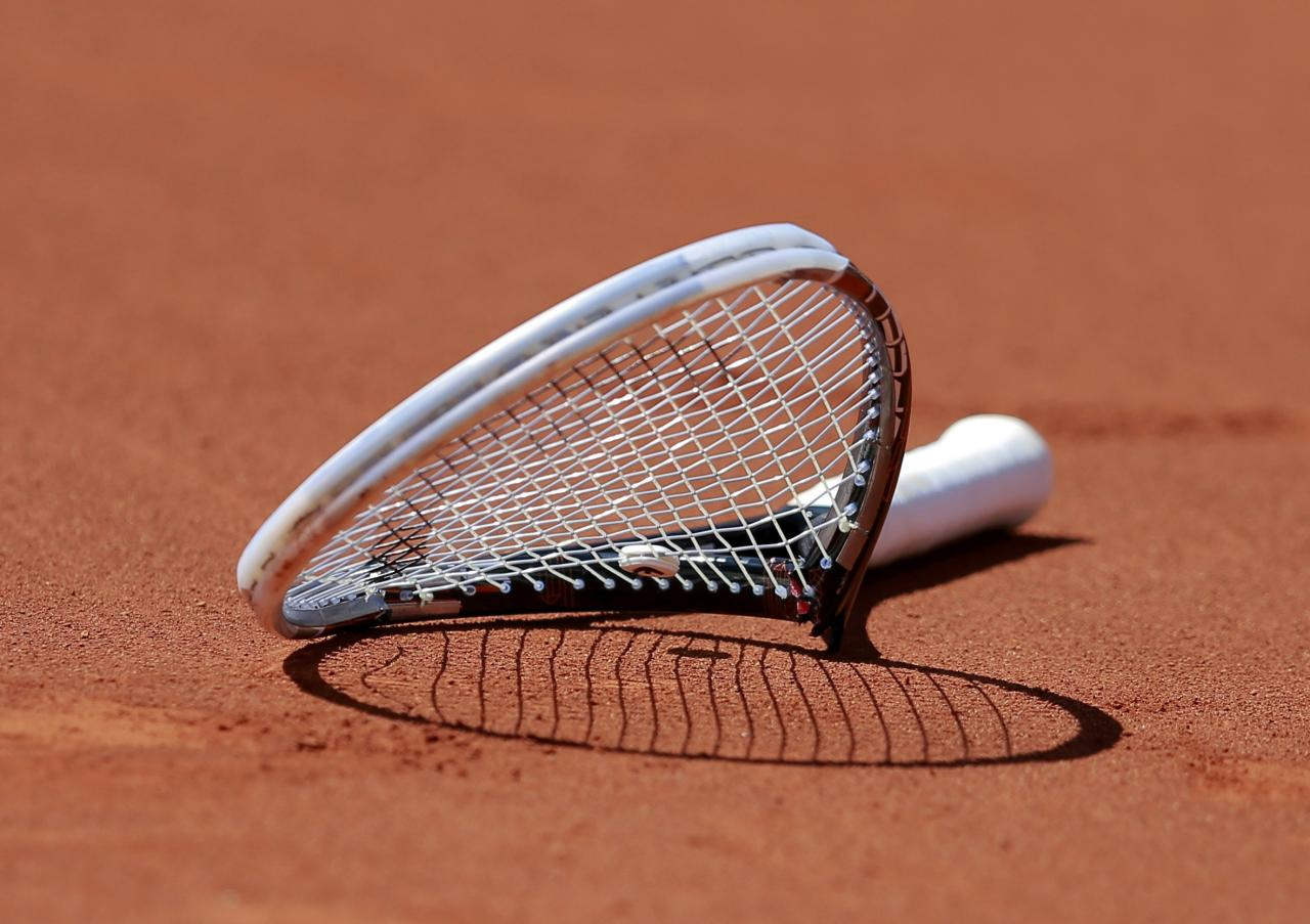 The broken racket of Novak Djokovic of Serbia is seen on the court after he smashed it during his men's semi-final match against Ernests Gulbis of Latvia at the French Open tennis tournament at the Roland Garros stadium in Paris June 6, 2014. REUTERS/Vincent Kessler (FRANCE - Tags: SPORT TENNIS TPX IMAGES OF THE DAY)