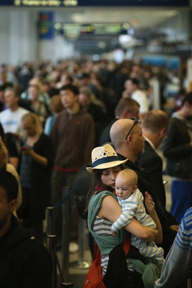 CHICAGO, IL - APRIL 16:  American Airlines passengers Chelsea Hunt and her six-month-old baby Lucas wait in line with other passengers to reschedule flights at O'Hare Airport on April 16, 2013 in Chicago, Illinois.  Thousands of American Airlines travelers became stranded today when the airline was forced to ground all its flights after a nationwide problem with its computer systems.  (Photo by Scott Olson/Getty Images)