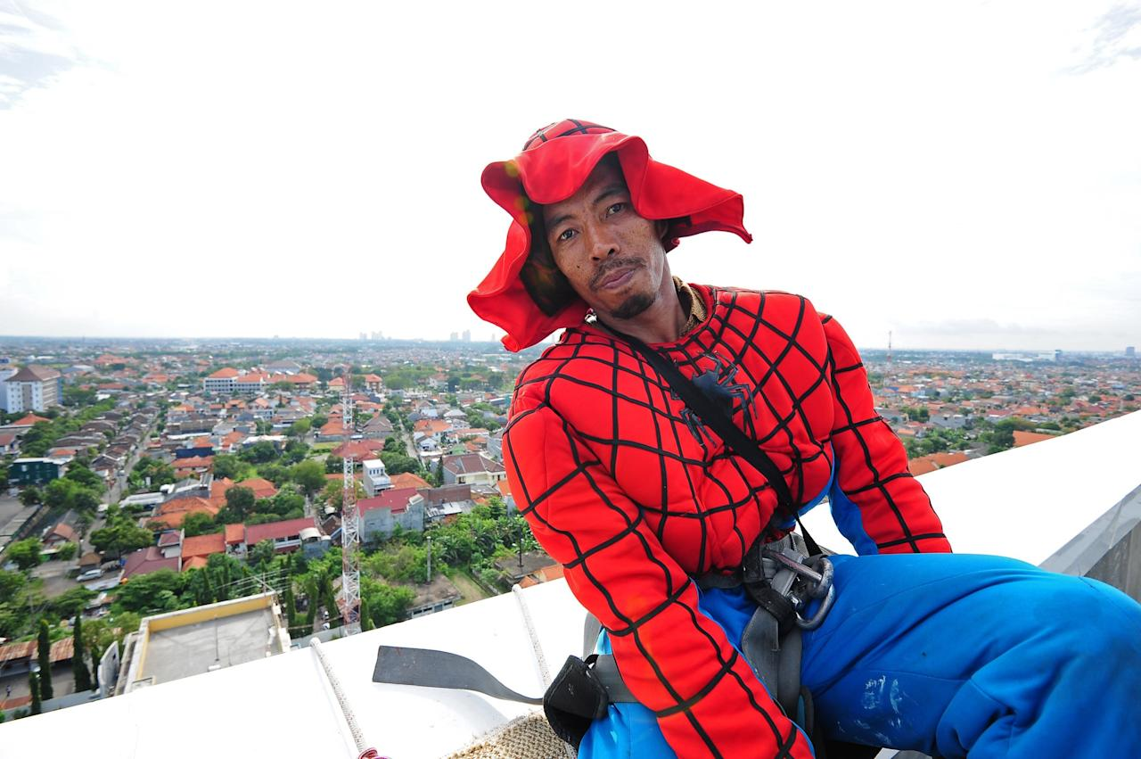 SURABAYA, INDONESIA - JULY 12: Indonesian 'Spider-Man' window cleaner, 37-year-old Teguh is seen without a mask as he takes a break from cleaning the glass windows of the 18-storey Alana Hotel on July 12, 2013 in Surabaya, Indonesia. Teguh is a specialist glass window cleaner working on high-rise buildings wearing a Spider-Man uniform and working at an altitude of over 500 meters above ground level. He earns between Rp. 5 million and 15 million depending on the height of the building and the level of difficulty. (Photo by Robertus Pudyanto/Getty Images)