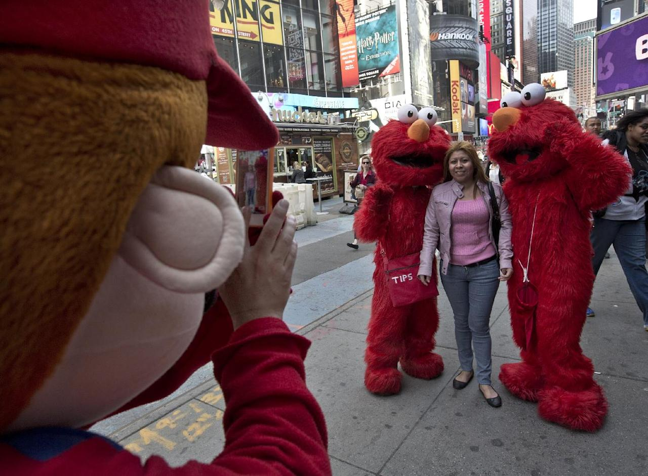 A Super Mario character, left, uses a woman's mobile phone camera to photographer her with a pair of Elmo characters in New York's Times Square, Tuesday, April 9, 2013. A string of arrests in the last few months has brought unwelcome attention to the growing number of people, mostly poor immigrants, who make a living by donning character outfits, roaming Times Square and charging tourists a few dollars to pose with them in photos. (AP Photo/Richard Drew)