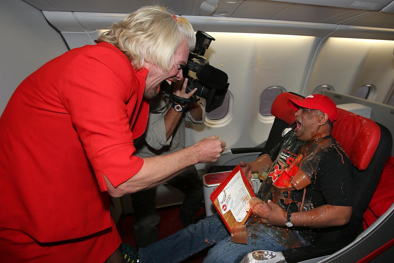 PERTH, AUSTRALIA - MAY 12:  Sir Richard Branson tips a tray of drinks onto Tony Fernandes prior to their flight to Kuala Lumpur at Perth International Airport on May 12, 2013 in Perth, Australia. Sir Richard Branson lost a friendly bet to AirAsia Group Chief Executive Officer Tony Fernandez after wagering on which of their Formula One racing teams would finish ahead of each other in their debut season of the 2010 Formula One Grand Prix in Abu Dhabi and that the loser would serve as a female flight attendant on board the winner's airline.  (Photo by Paul Kane/Getty Images)