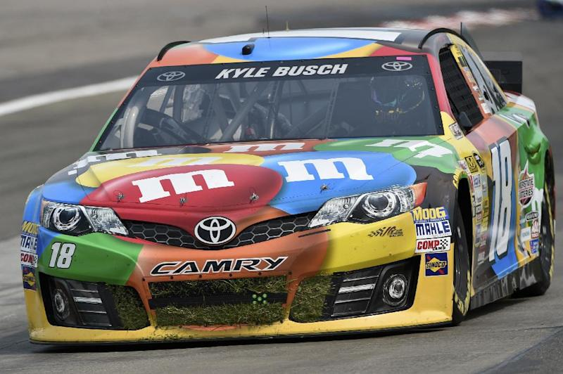 In this Aug. 8, 2014, file photo, the grille of Kyle Busch's (18) race car is full of grass after he went off course during a practice session for a NASCAR Sprint Cup Series auto race at Watkins Glen International in Watkins Glen N.Y.  Mars has signed multi-year sponsorship deals with both Joe Gibbs Racing and NASCAR. The agreement announced Wednesday, Aug. 13, 2014,  keeps Mars on the No. 18 Toyota driven by Kyle Busch