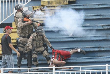 Policemen fire rubber bullets as they help an Atletico Paranaense fan in Joinville