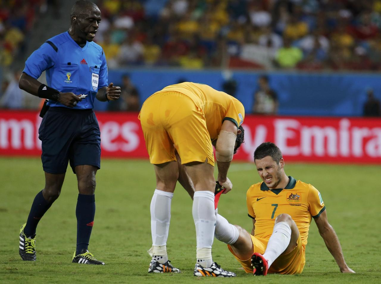 Australia's Matthew Leckie (bottom R) grimaces on the pitch, near referee Noumandiez Doue of Ivory Coast (L), during the team's 2014 World Cup Group B soccer match against Chile at the Pantanal arena in Cuiaba June 13, 2014. REUTERS/Eric Gaillard (BRAZIL - Tags: SOCCER SPORT WORLD CUP)