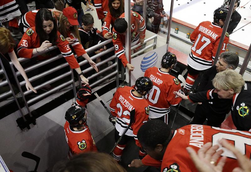 Chicago Blackhawks fans greet with players before they get on the ice before Game 2 of the Western Conference finals in the NHL hockey Stanley Cup playoffs against the Los Angeles Kings in Chicago on Wednesday, May 21,  2014