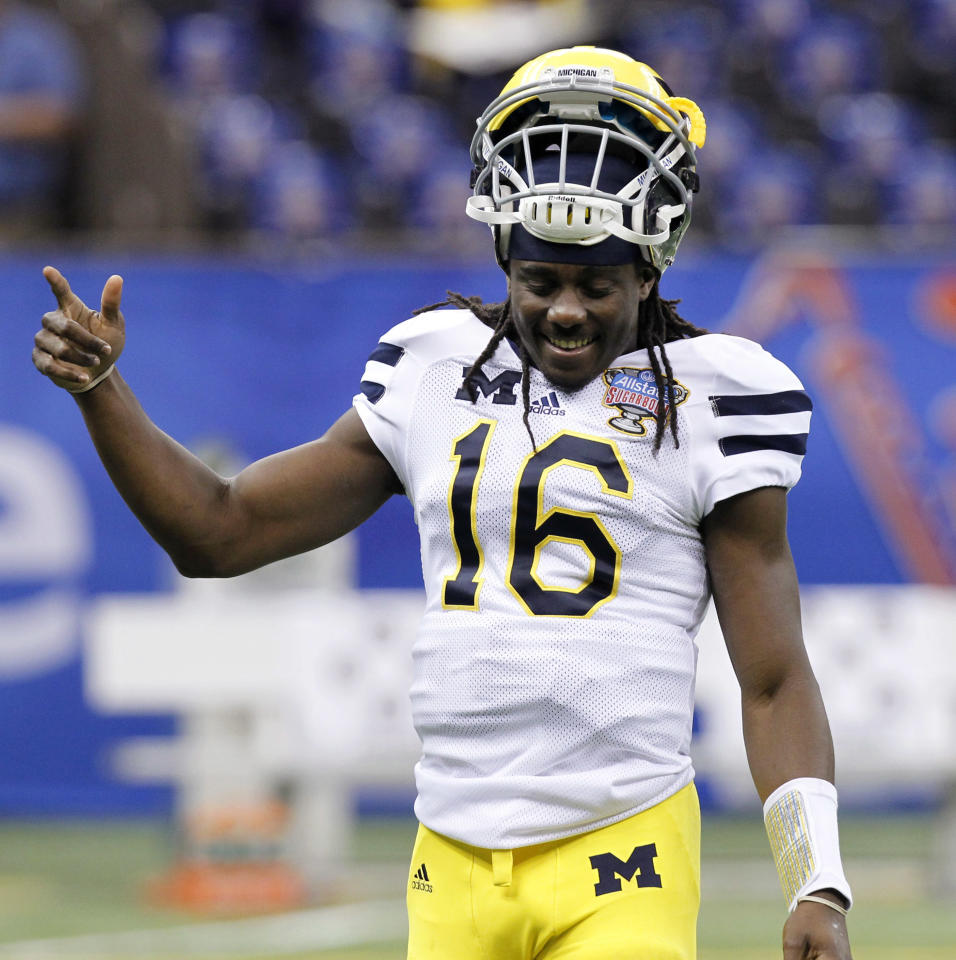 Michigan quarterback Denard Robinson (16) smiles as he warms up for the Sugar Bowl NCAA college football game against Virginia Tech, in New Orleans on Tuesday, Jan. 3, 2012. (AP Photo/Gerald Herbert)