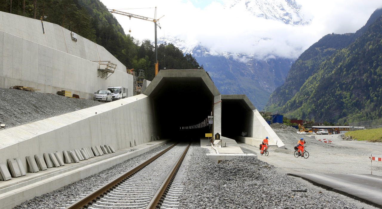 Workers cycle past the northern entrances of the NEAT Gotthard Base tunnel near Erstfeld May 7, 2012. Crossing the Alps, the world's longest train tunnel should become operational at the end of 2016. The project consists of two parallel single track tunnels, each of a length of 57 km (35 miles)     REUTERS/Arnd Wiegmann   (SWITZERLAND - Tags: BUSINESS CONSTRUCTION EMPLOYMENT TRAVEL) - RTR31QCK