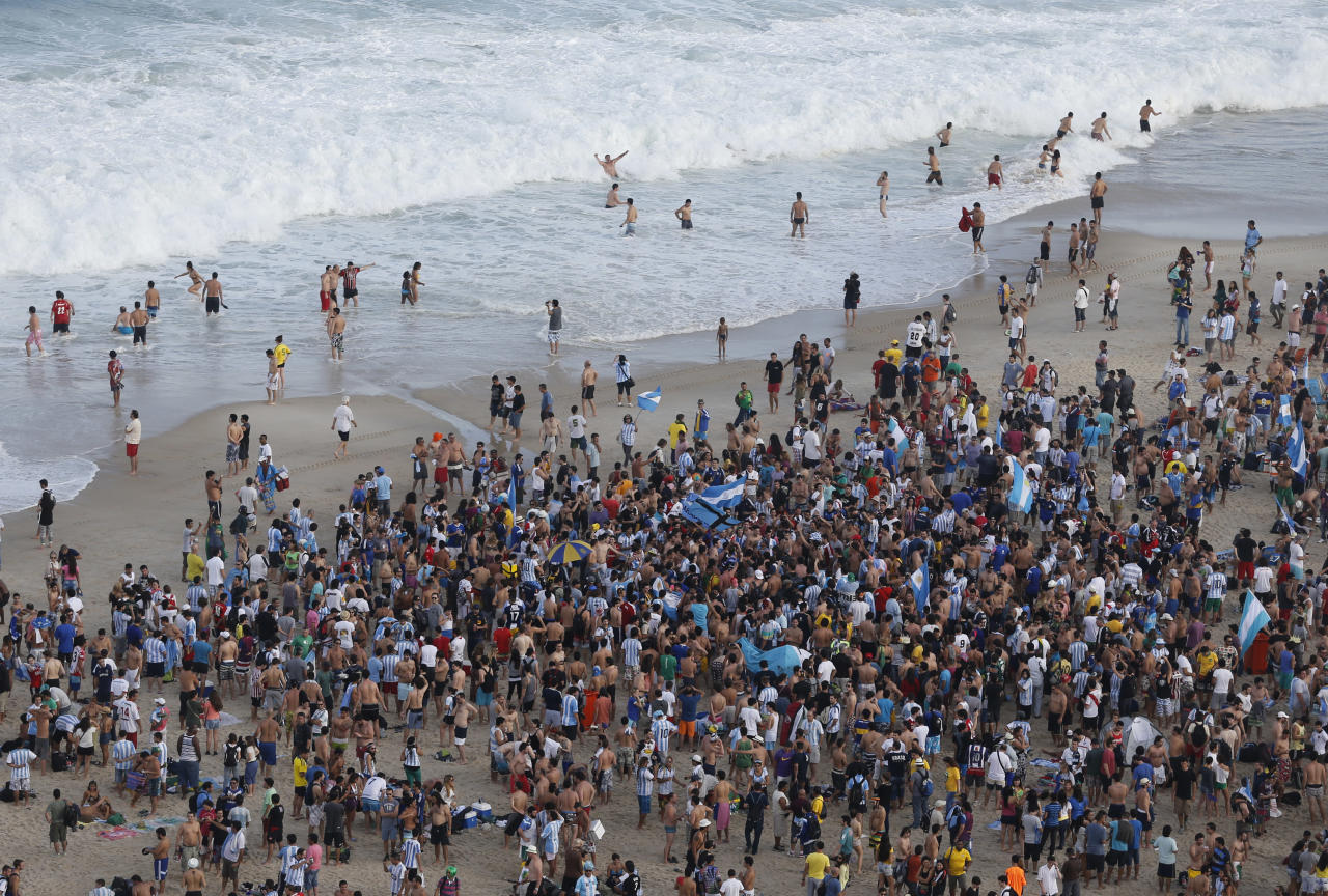 Soccer fans of the Argentina's national soccer team sing and dance on Copacabana beach, in Rio de Janeiro, Brazil, Saturday, July 12, 2014. Argentina will face Germany in the World Cup final, Sunday. (AP Photo/Silvia Izquierdo)