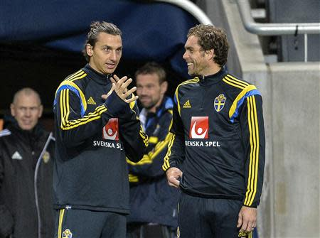 Sweden's Ibrahimovic talks to teammate Elmander during a soccer training session in Stockholm